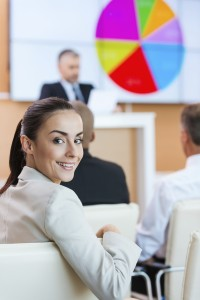 Businesswoman at the conference. Confident young woman in formalwear looking over shoulder and smiling while sitting at the conference hall with public speaker in the background